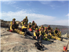 Crew members taking a break on a mountain after fighting a fire