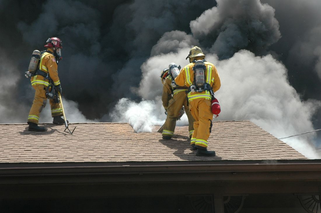 Three firefighters on the roof of house covered in smoke putting fire out