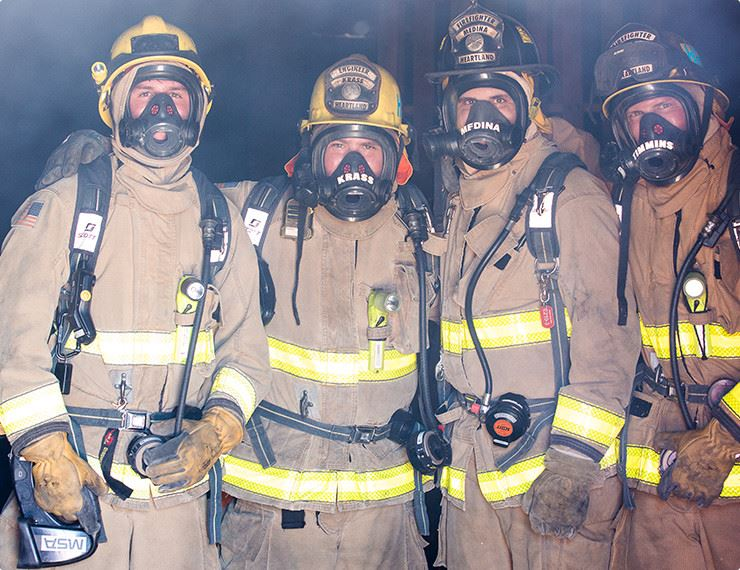 Firefighters in full gear posing for photo