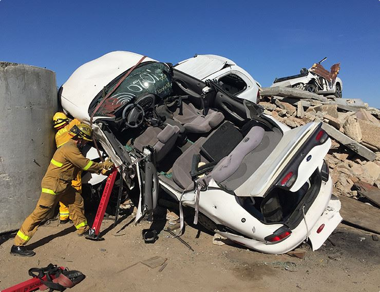 Firefighters training with wrecked vehicle