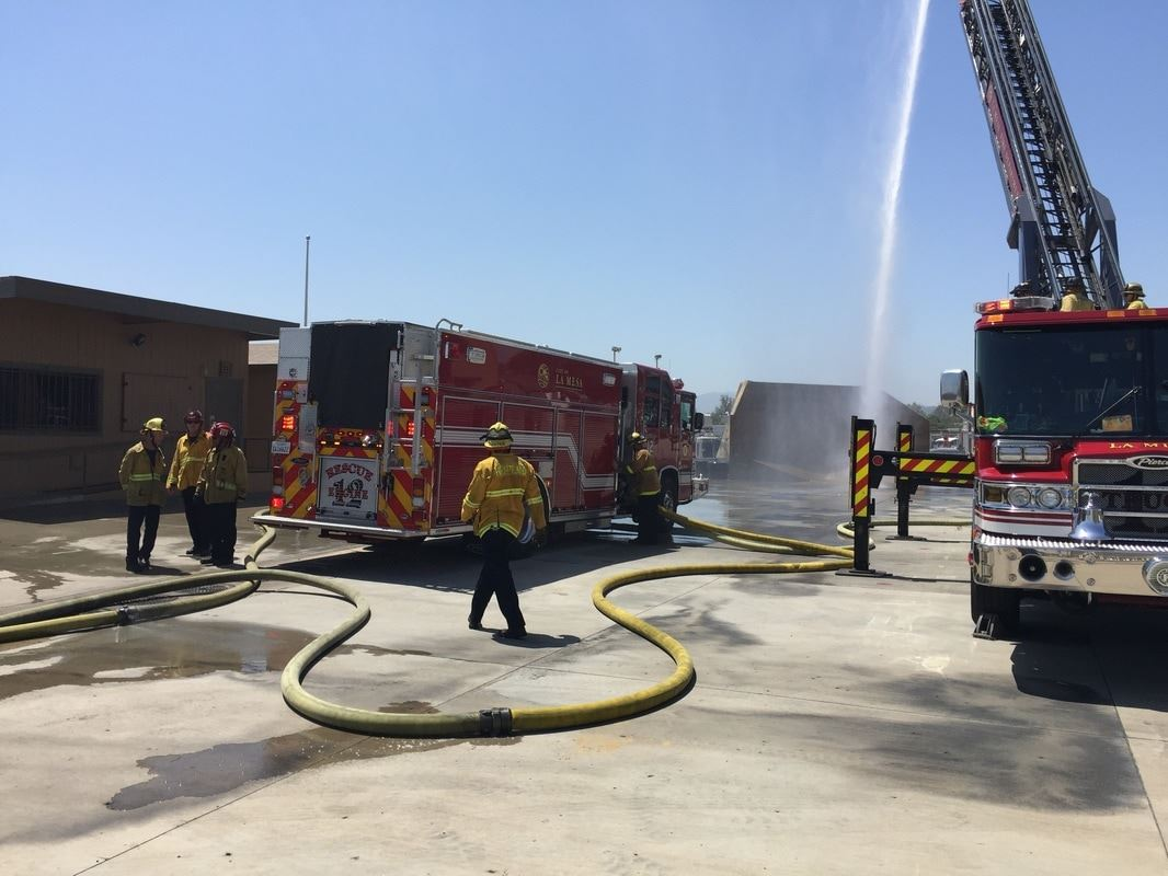 Fire Trucks and Personnel by Fire Hose Spraying Water 1