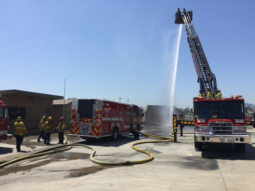 Fire Trucks and Personnel by Fire Hose Spraying Water 2