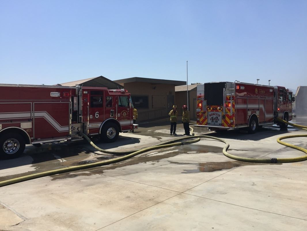 Fire Trucks and Personnel by Fire Hose