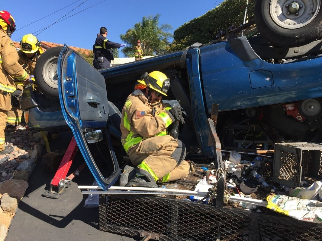 Firefighter Kneeling by Open Door of Upside down Truck