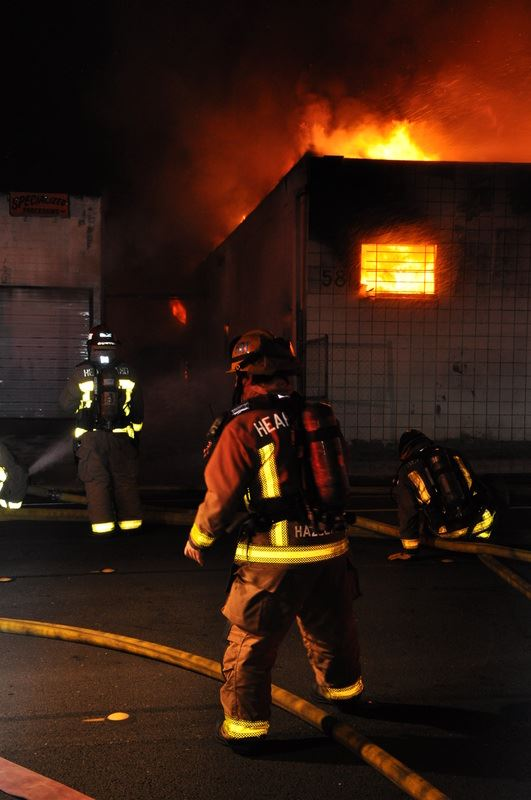 Two firefighters standing in front of burning building