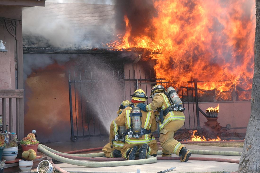 Three firefighters holding fire hose in front of burning house