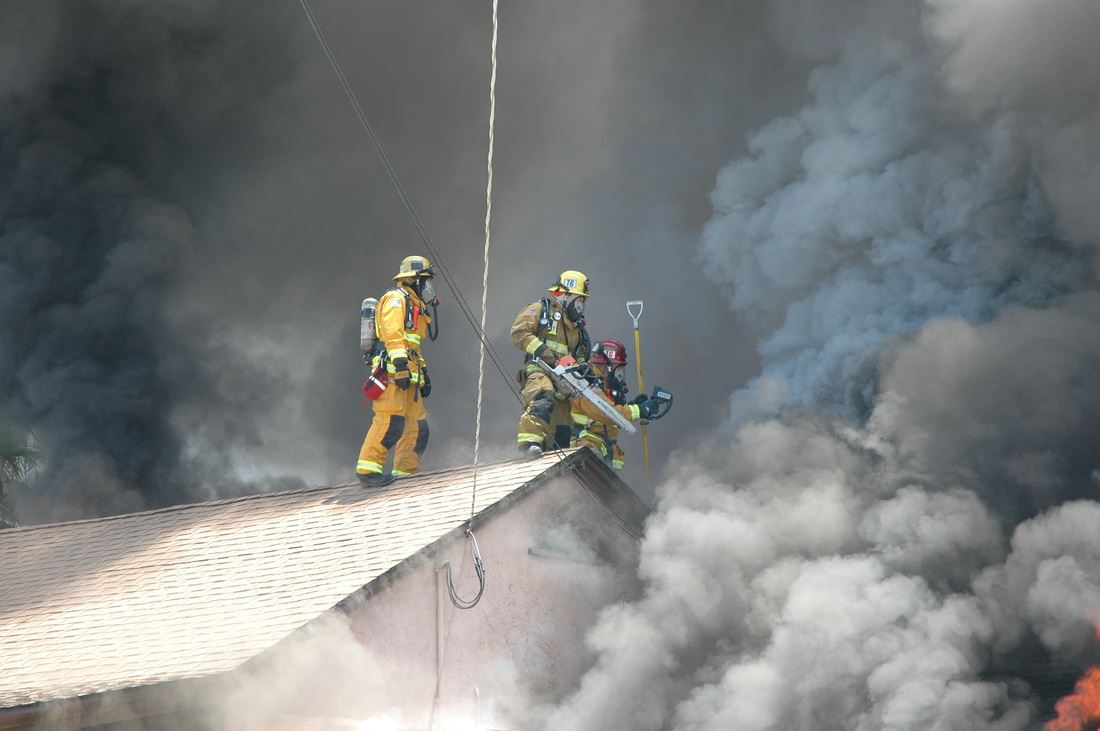 Three firefighters on the roof of house covered in smoke